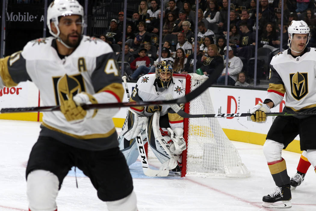 Vegas Golden Knights center Pierre-Edouard Bellemare (41) and defenseman Colin Miller (6) skate towards the action as goaltender Marc-Andre Fleury (29) defends the net during the second period aga ...