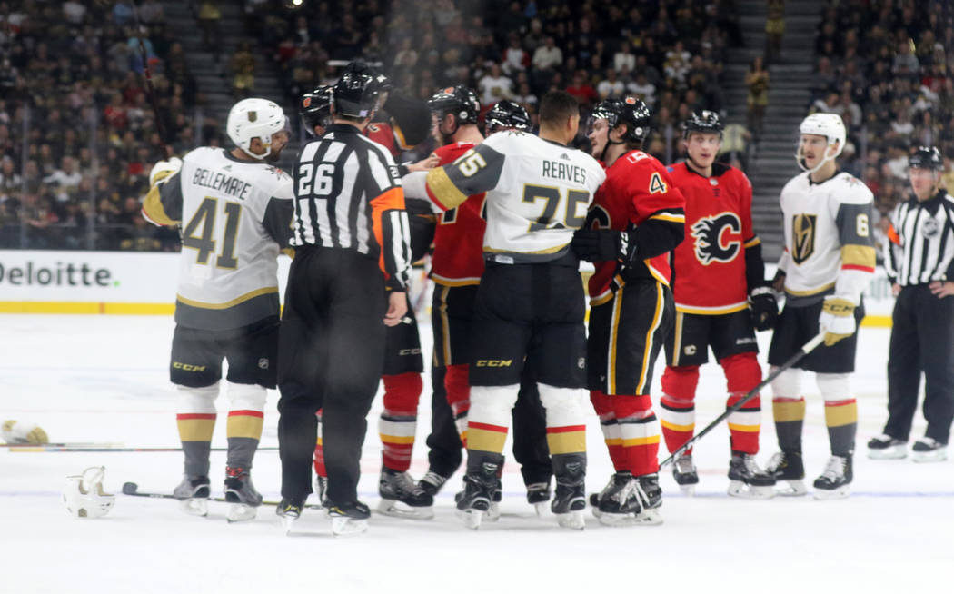 Vegas Golden Knights center Pierre-Edouard Bellemare (41) and defenseman Colin Miller (6) remain on the ice after right wing Ryan Reaves (75) and Calgary Flames center Mark Jankowski (77) clash du ...