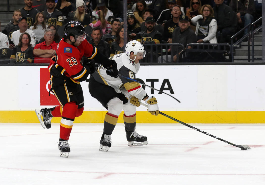 Vegas Golden Knights defenseman Colin Miller (6) skates with the puck as Calgary Flames center Dillon Dube (29) tries to chase after the puck during the second period of an NHL game in Las Vegas, ...