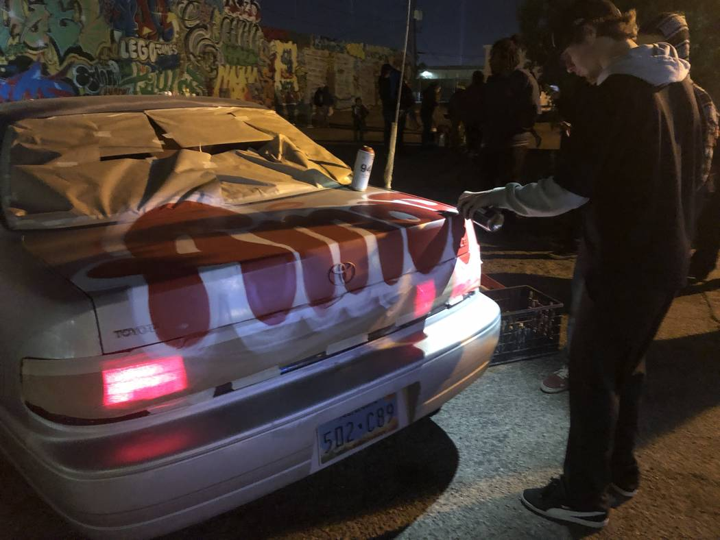 "A graffiti artists spray paints ""amore"" onto a car at a vigil for George Campoverde on Saturday, November 24, 2018. The 29-year-old, whose daughter's middle name is Amore, died Wednesday, November ..."