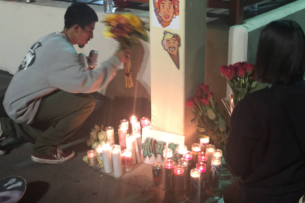 Two friends of George Campoverde arrange flowers and candles at the Winchester Cultural Center's skate park in east Las Vegas on Friday, November 23, 2018. Campoverde, 29, died Wednesday, November ...