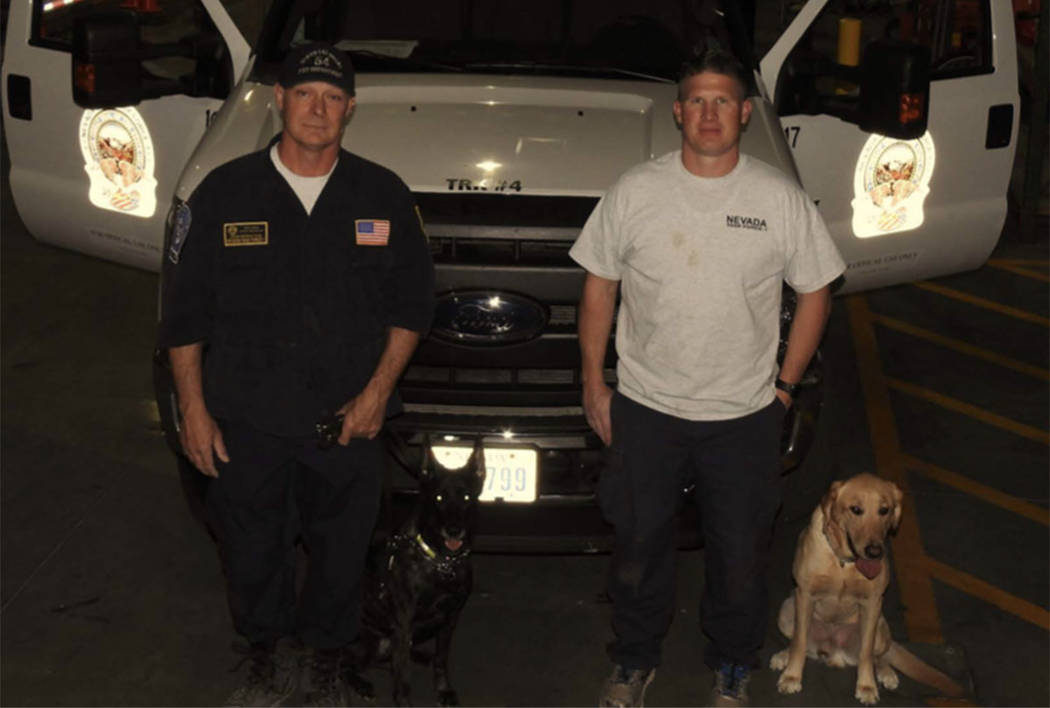Dog handlers pose with Kya, left, and Dexter, right. (Clark County Fire Department)