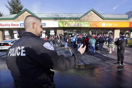 A Kirkland police officer directs traffic past a closed frozen-yogurt shop where Byron Ragland and local civil rights leaders addressed media members Tuesday, Nov. 20, 2018, in Kirkland, Wash. The ...