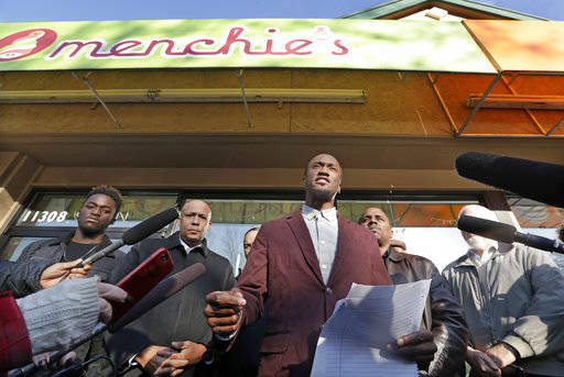 Byron Ragland addresses reporters in front of a frozen-yogurt shop Tuesday, Nov. 20, 2018, in Kirkland, Wash. The police department there has apologized for an incident in which officers helped th ...