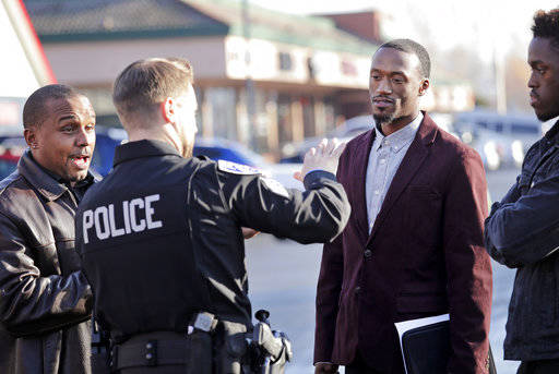 Byron Ragland, second right, talks with Kirkland police Sgt. Eric Karp as Gerald Hankerson, left, president of the Seattle King County NAACP, looks on near a frozen-yogurt shop that Ragland was ki ...
