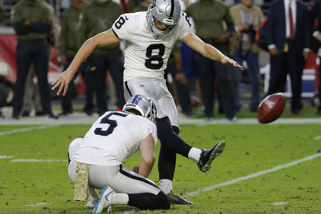 Oakland Raiders kicker Daniel Carlson (8) kicks the game winning field goal as punter Johnny Townsend (5) holds during the second half of an NFL football game against the Arizona Cardinals, Sunday ...
