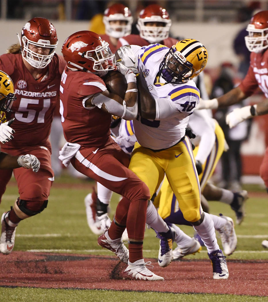 Arkansas running back Rakeem Boyd is tackled by LSU defender Devin White during the second half of an NCAA college football game, Saturday, Nov. 10, 2018, in Fayetteville, Ark. (AP Photo/Michael W ...