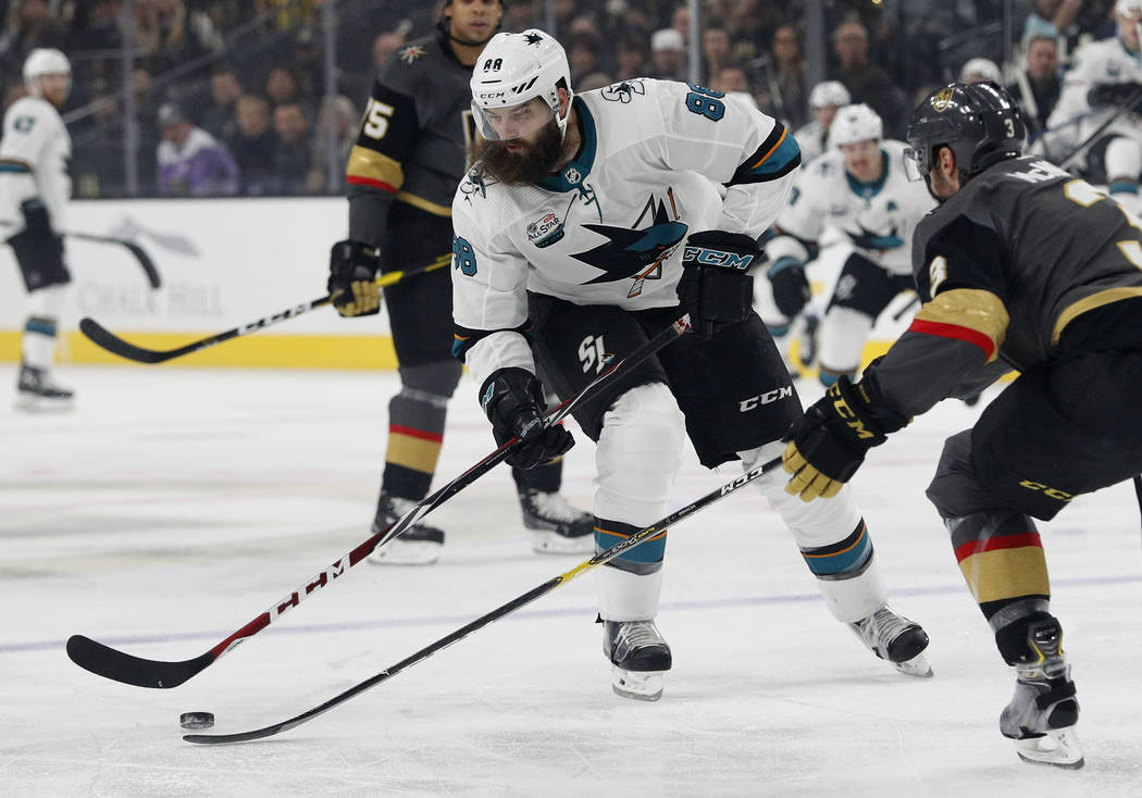 San Jose Sharks defenseman Brent Burns, left, tries to skate around Vegas Golden Knights defenseman Brayden McNabb during the first period of an NHL hockey game Saturday, Nov. 24, 2018, in Las Veg ...