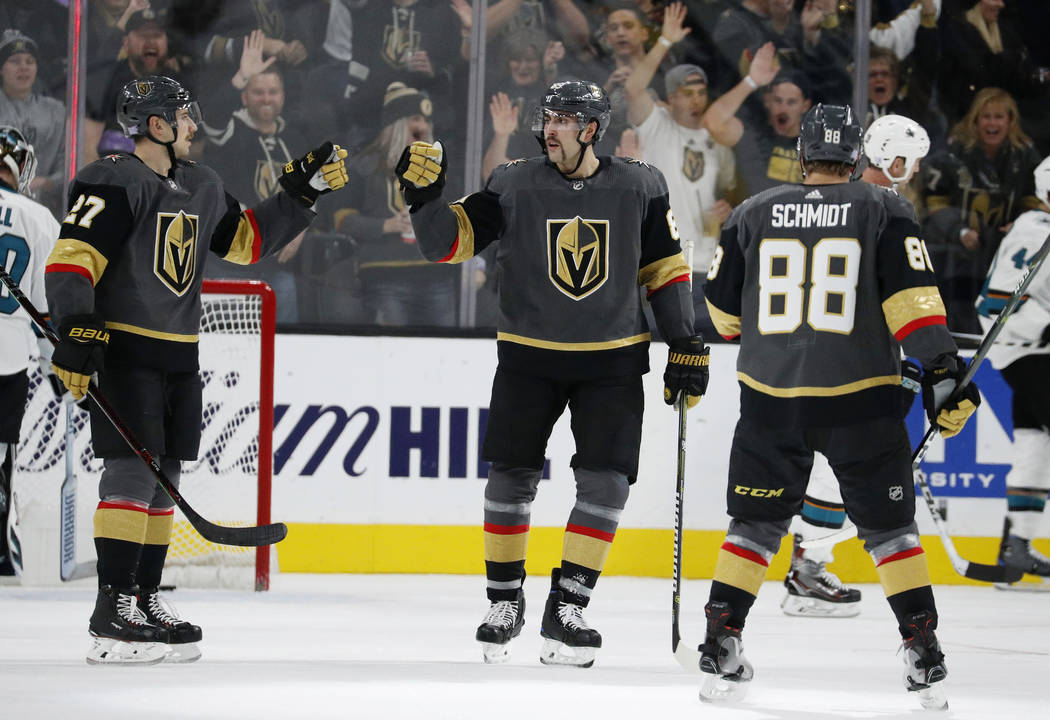 Vegas Golden Knights defenseman Shea Theodore, left, celebrates after right wing Alex Tuch, center, scored against the San Jose Sharks during the third period of an NHL hockey game Saturday, Nov. ...