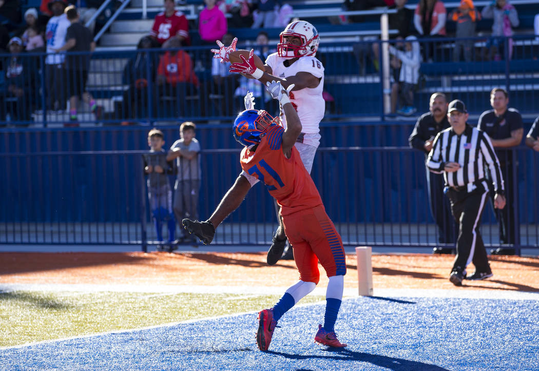 Liberty wide receiver Maurice Hampton (16) pulls in the ball in the end zone for a touchdown over Bishop Gorman's Ammonte Beverly (21) during the first half of the NIAA 4A Desert Region championsh ...