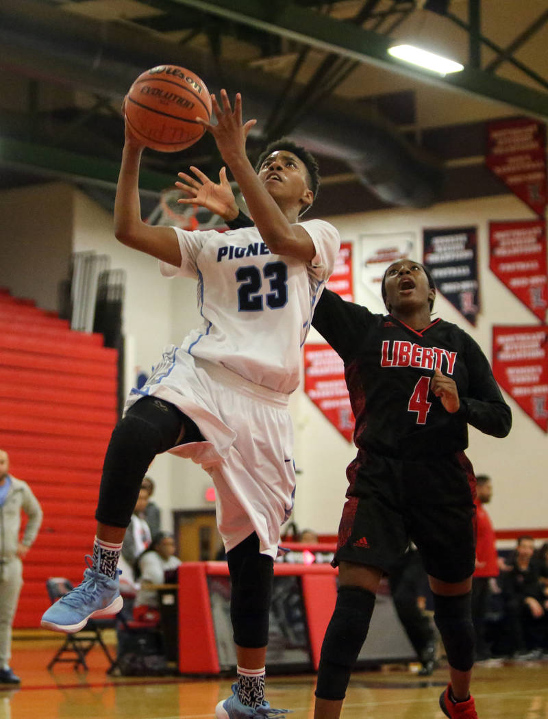 Canyon Springs' Kayla Johnson (23) looks to shoot while Liberty's Robin Walker (4) trails behind during the second half of the Championship game of the Liberty Thanksgiving Invitational girls bask ...