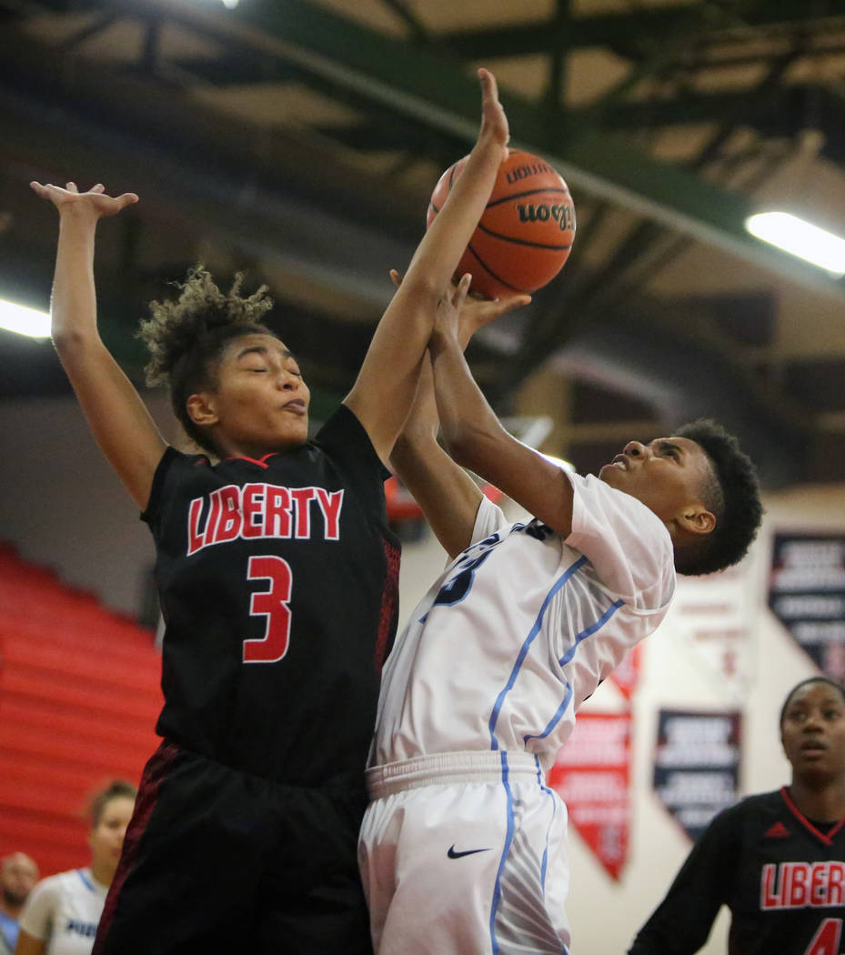 Canyon Springs' Kayla Johnson (23) jumps up with the ball while being guarded by Liberty's Journie Augmon (3) during the second half of the Championship game of the Liberty Thanksgiving Invitation ...