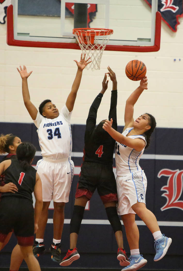 Canyon Spring's Ja'moni Brown (34), left, and Jeanette Fine (11) block the ball from Liberty's Robin Walker (4) during the second half of the Championship game of the Liberty Thanksgiving Invitat ...