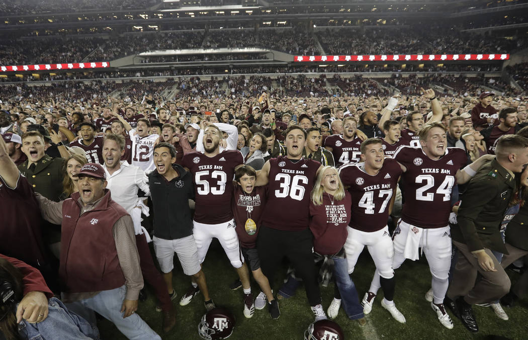 Fans and students join Texas A&M football players on the field after an NCAA college football game against LSU Saturday, Nov. 24, 2018, in College Station, Texas. Texas A&M won 74-72 in se ...