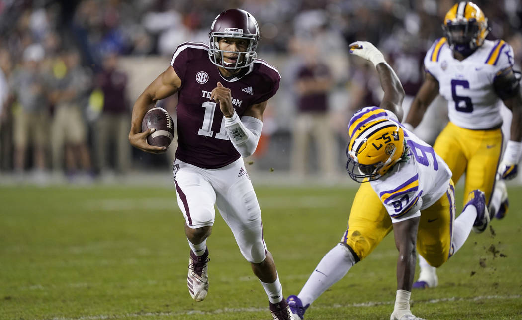 Texas A&M quarterback Kellen Mond (11) breaks away from LSU defensive end Glen Logan (97) during the first half of an NCAA college football game Saturday, Nov. 24, 2018, in College Station, Te ...