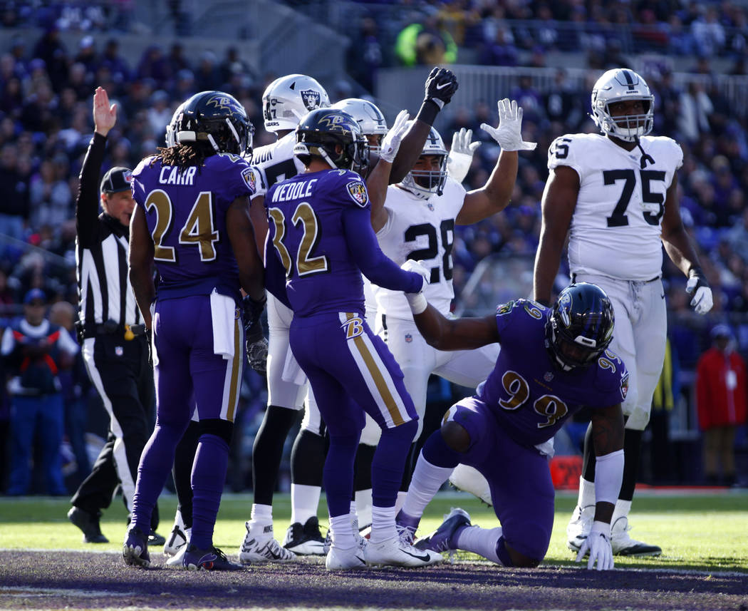 Oakland Raiders running back Doug Martin (28) celebrates his touchdown as offensive tackle Brandon Parker (75) walks nearby Baltimore Ravens cornerback Brandon Carr (24), free safety Eric Weddle ( ...