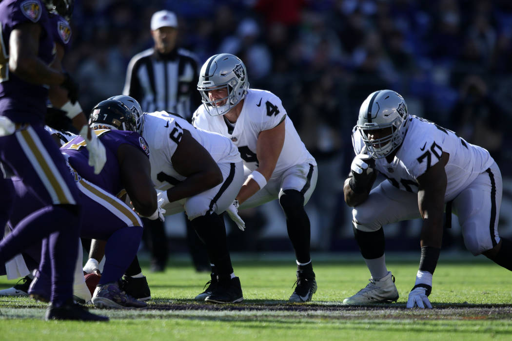 Oakland Raiders quarterback Derek Carr (4) waits for the snap as offensive guard Kelechi Osemele (70) and center Rodney Hudson (61) prepare to block for him during the first half of an NFL game in ...