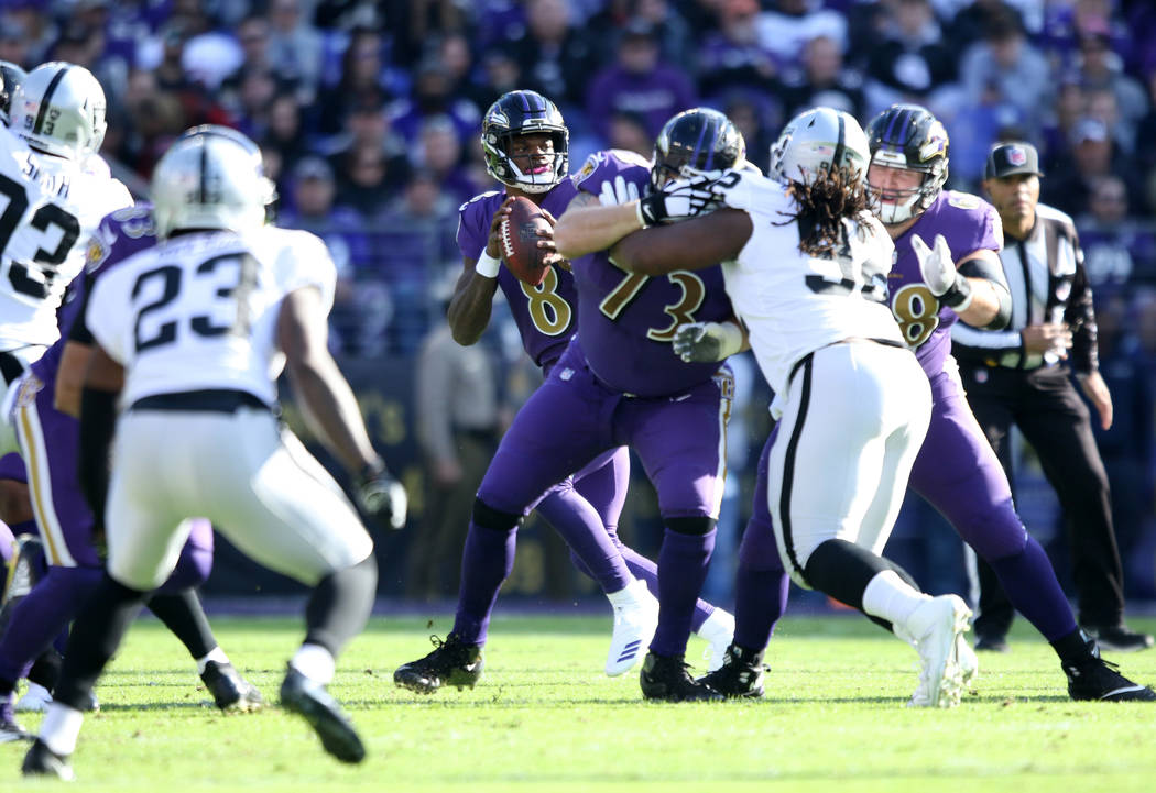 Baltimore Ravens quarterback Lamar Jackson (8) drops back to pass during the first half of an NFL game against the Oakland Raiders in Baltimore, Md., Sunday, Nov. 25, 2018. Heidi Fang Las Vegas Re ...