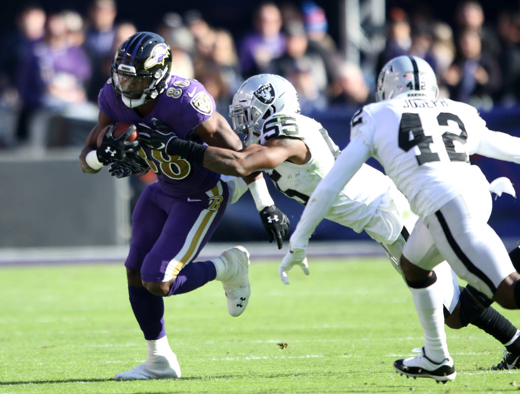 Baltimore Ravens running back Ty Montgomery (88) runs with the football as Oakland Raiders middle linebacker Marquel Lee (55) goes for the tackle during the first half of an NFL game in Baltimore, ...