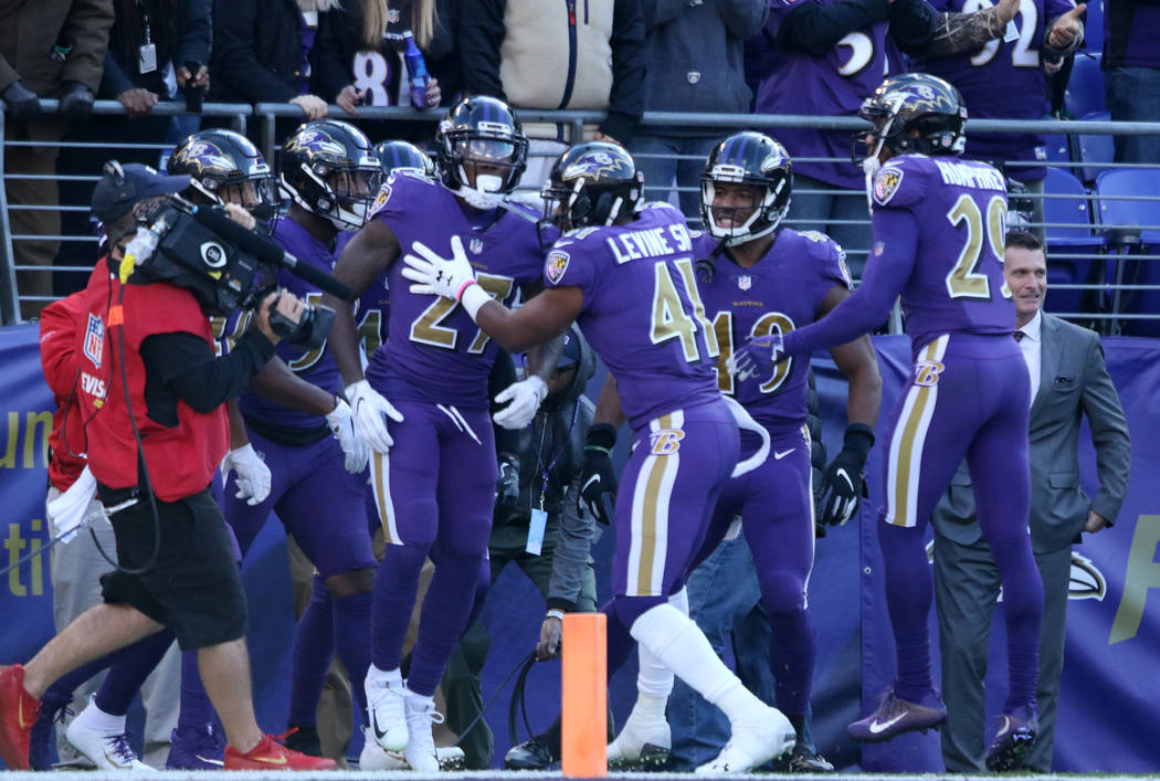 The Baltimore Ravens defensive unit celebrates cornerback Cyrus Jones' (27) punt returned for a touchdown during the first half of an NFL game against the Oakland Raiders in Baltimore, Md., Sunday ...
