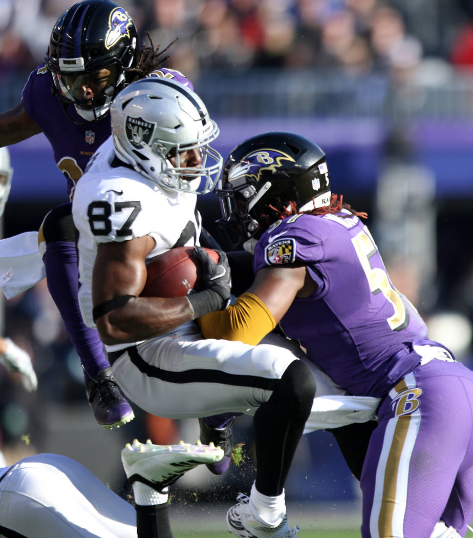 Oakland Raiders tight end Jared Cook (87) is tackled by Baltimore Ravens inside linebacker C.J. Mosley (57) during the first half of an NFL game in Baltimore, Md., Sunday, Nov. 25, 2018. Heidi Fan ...