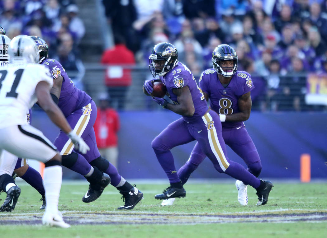 Baltimore Ravens quarterback Lamar Jackson (8) hands off the football to running back Gus Edwards (35) during the first half of an NFL game against the Oakland Raiders in Baltimore, Md., Sunday, N ...