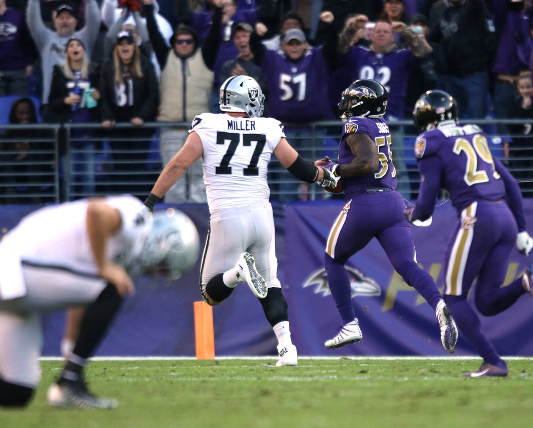 Baltimore Ravens outside linebacker Terrell Suggs (55) scores on an interception thrown by Oakland Raiders quarterback Derek Carr (4), kneeling, as offensive tackle Kolton Miller (77) tries to cha ...