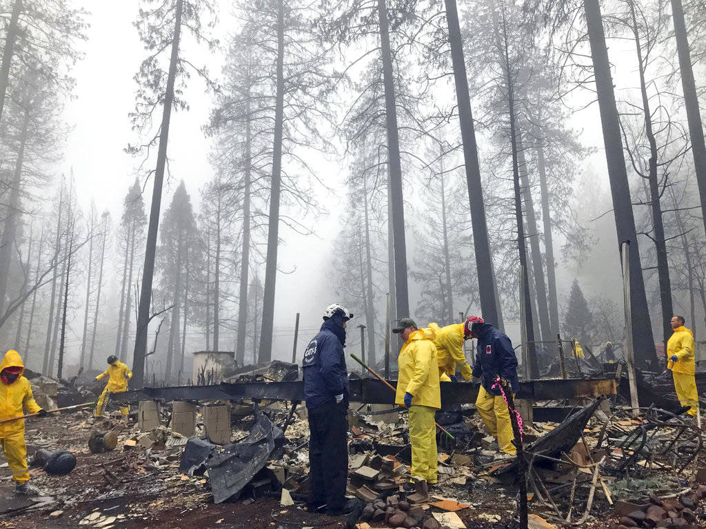 In this Nov. 23, 2018, file photo, after a brief delay to let a downpour pass, volunteers resume their search for human remains at a mobile home park in Paradise, Calif. A massive wildfire that ki ...