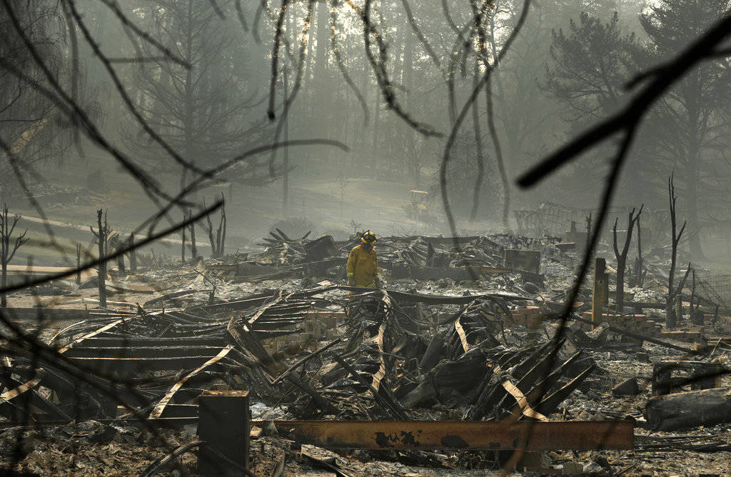 In this Nov. 16, 2018, file photo, a firefighter searches for human remains in a trailer park destroyed in the Camp Fire, in Paradise, Calif. The massive wildfire that killed dozens of people and ...