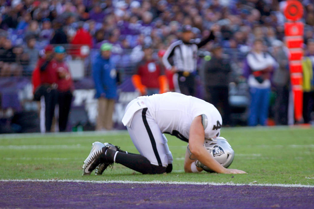 Oakland Raiders quarterback Derek Carr (4) remains on the field after being injured on a play during the first half of an NFL game against the Baltimore Ravens in Baltimore, Md., Sunday, Nov. 25, ...