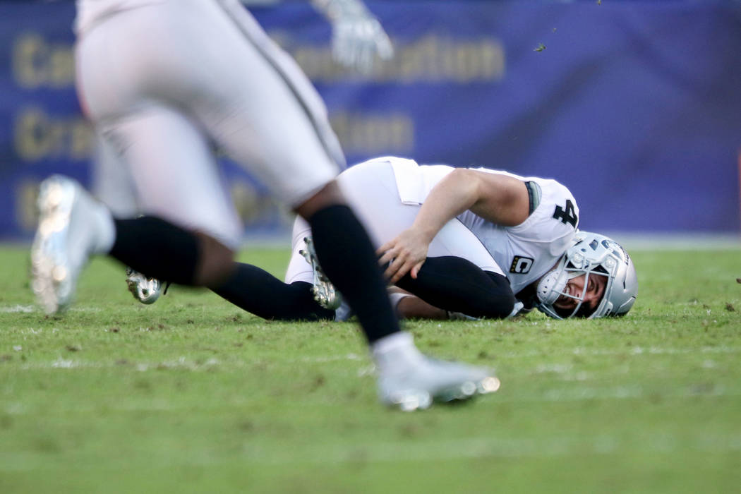 Oakland Raiders quarterback Derek Carr (4) grabs his leg on the field after being sacked by Baltimore Ravens outside linebacker Matt Judon (99), not pictured, during the second half of an NFL game ...