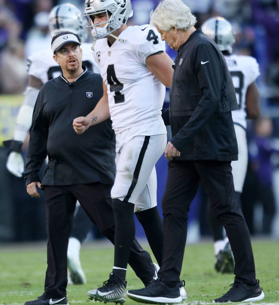 Oakland Raiders quarterback Derek Carr (4) comes off the field with trainers during the second half of an NFL game against the Baltimore Ravens in Baltimore, Md., Sunday, Nov. 25, 2018. Heidi Fang ...