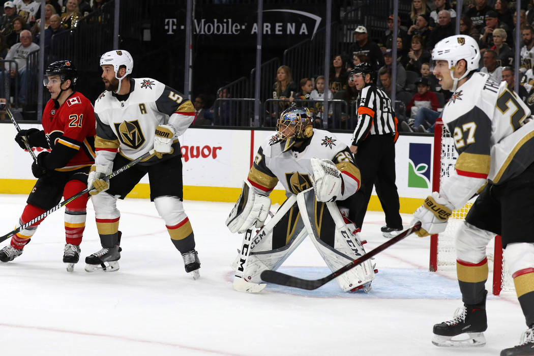 Calgary Flames right wing Garnet Hathaway (21) looks for the puck as Vegas Golden Knights goaltender Marc-Andre Fleury (29) is flanked by defenseman Deryk Engelland (5) and defenseman Shea Theodor ...