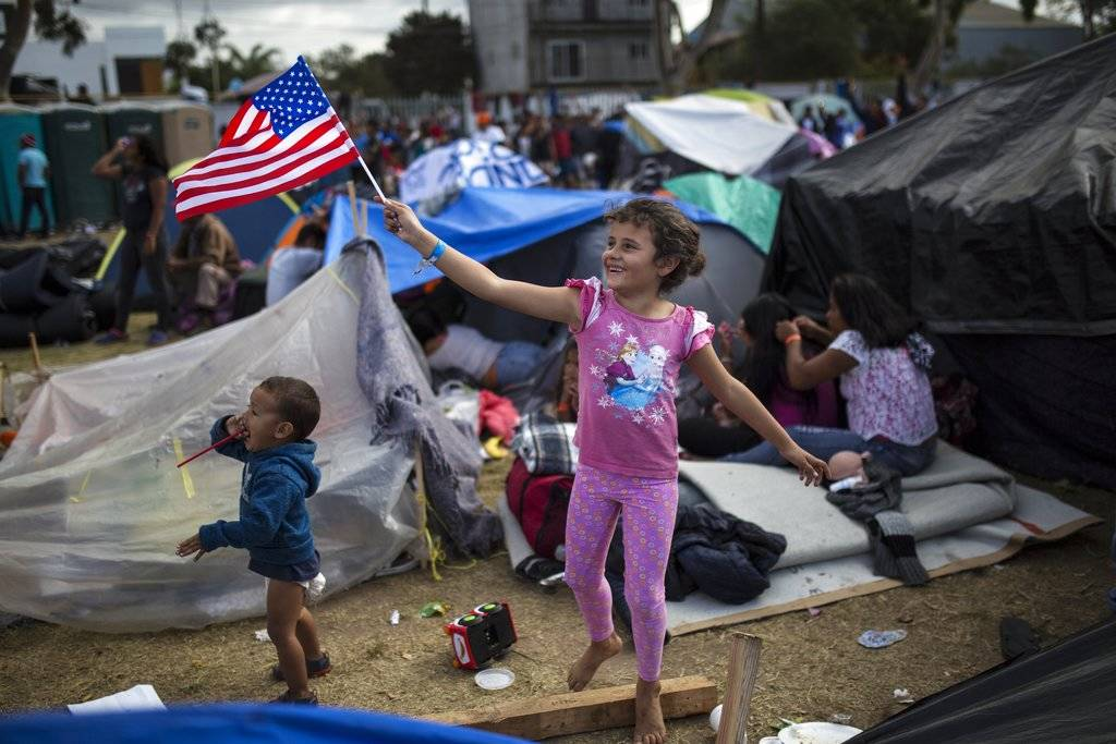Seven-year-old Honduran migrant Genesis Belen Mejia Flores waves an American flag at U.S. border control helicopters flying overhead near the Benito Juarez Sports Center serving as a temporary she ...