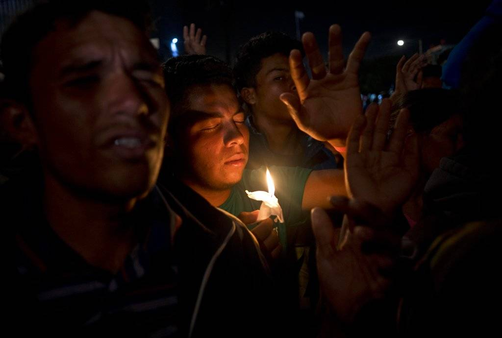 Migrants pray during a vigil outside the Benito Juarez Sports Center serving as a temporary shelter for Central American migrants in Tijuana, Mexico, Saturday, Nov. 24, 2018. The mayor of Tijuana ...