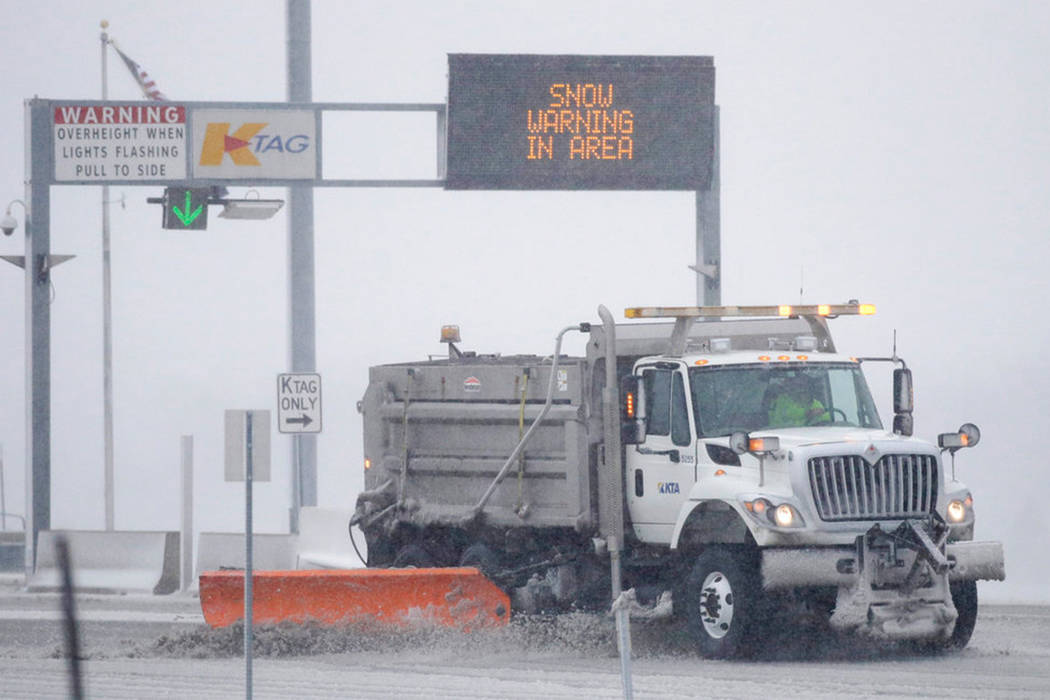 A plow removes snow at an entrance of the Kansas Turnpike near Lawrence, Kan., Sunday, Nov. 25, 2018. The area is under a blizzard warning. (AP Photo/Orlin Wagner)