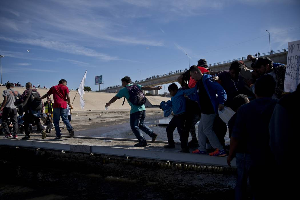 Migrants cross the river at the Mexico-U.S. border after getting past a line of Mexican police at the Chaparral crossing in Tijuana, Mexico, Sunday, Nov. 25, 2018, as they try to reach the U.S. T ...