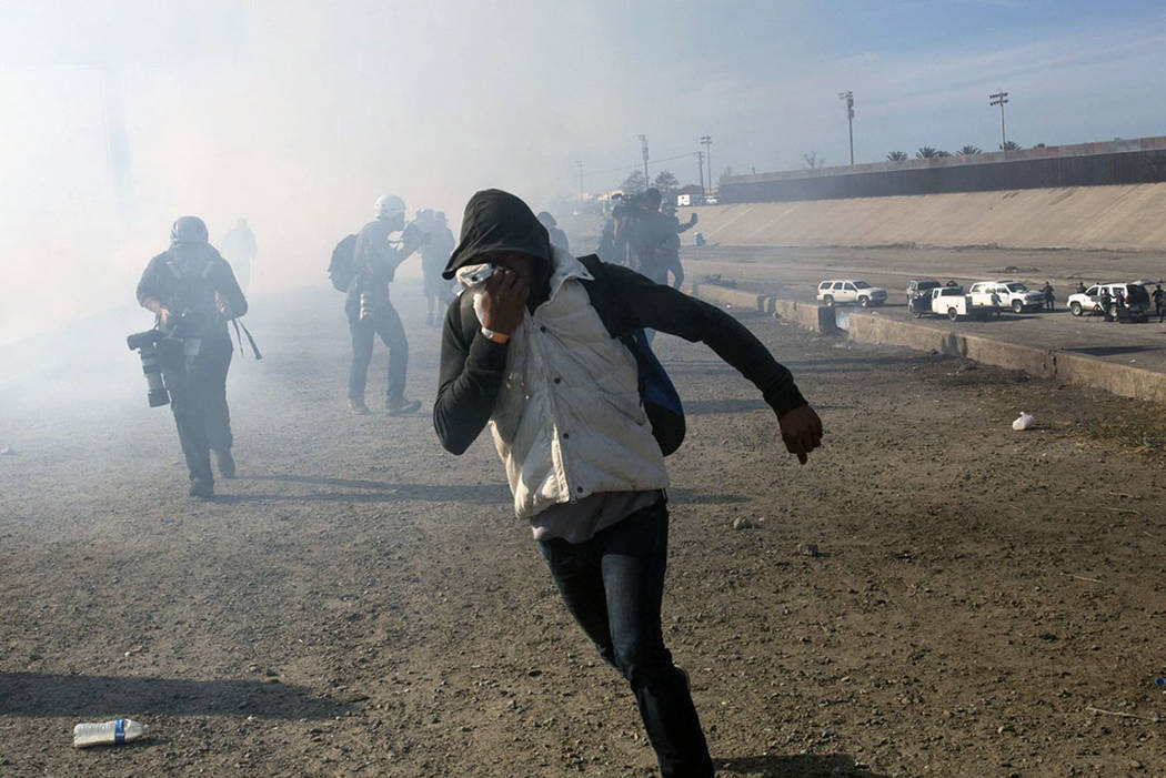 A migrant runs from tear gas launched by U.S. agents, amid members of the press covering the Mexico-U.S. border, after a group of migrants got past Mexican police at the Chaparral crossing in Tiju ...