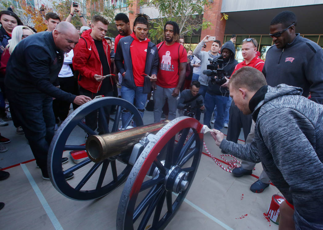 UNLV students and officials watch as Rebels football players, including kicker Evan Pantels, right, and head coach Tony Sanchez, far left, brush red paint on the Fremont Cannon outside of the Stud ...