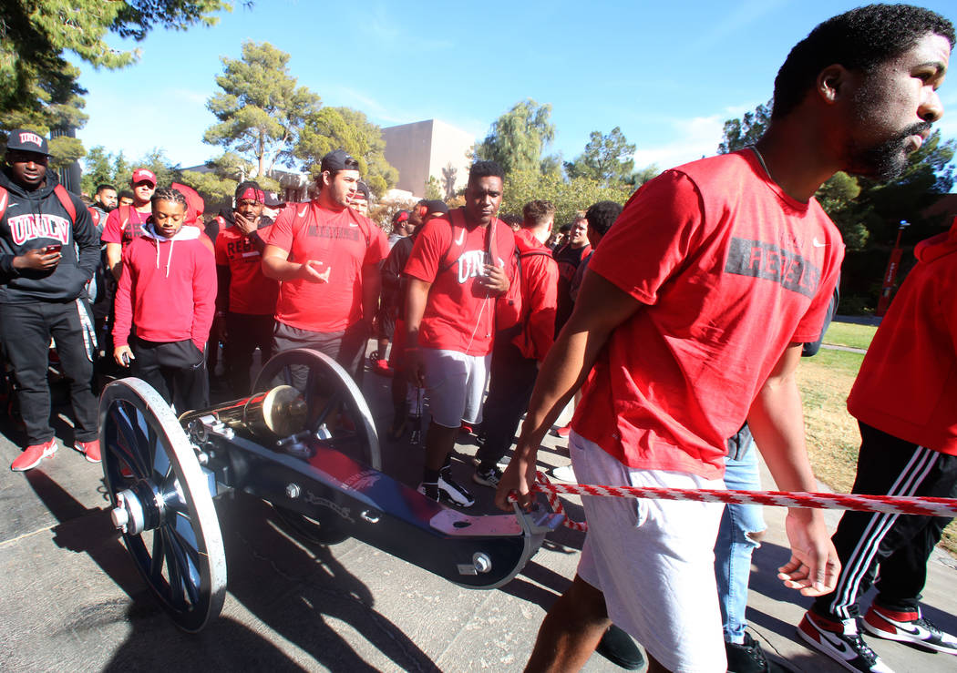 UNLV football players, including quarterback Armani Rogers, front, pull the Fremont Cannon to be painted red outside of the Student Union at UNLV on Monday, Nov, 26, 2019, in celebration of their ...
