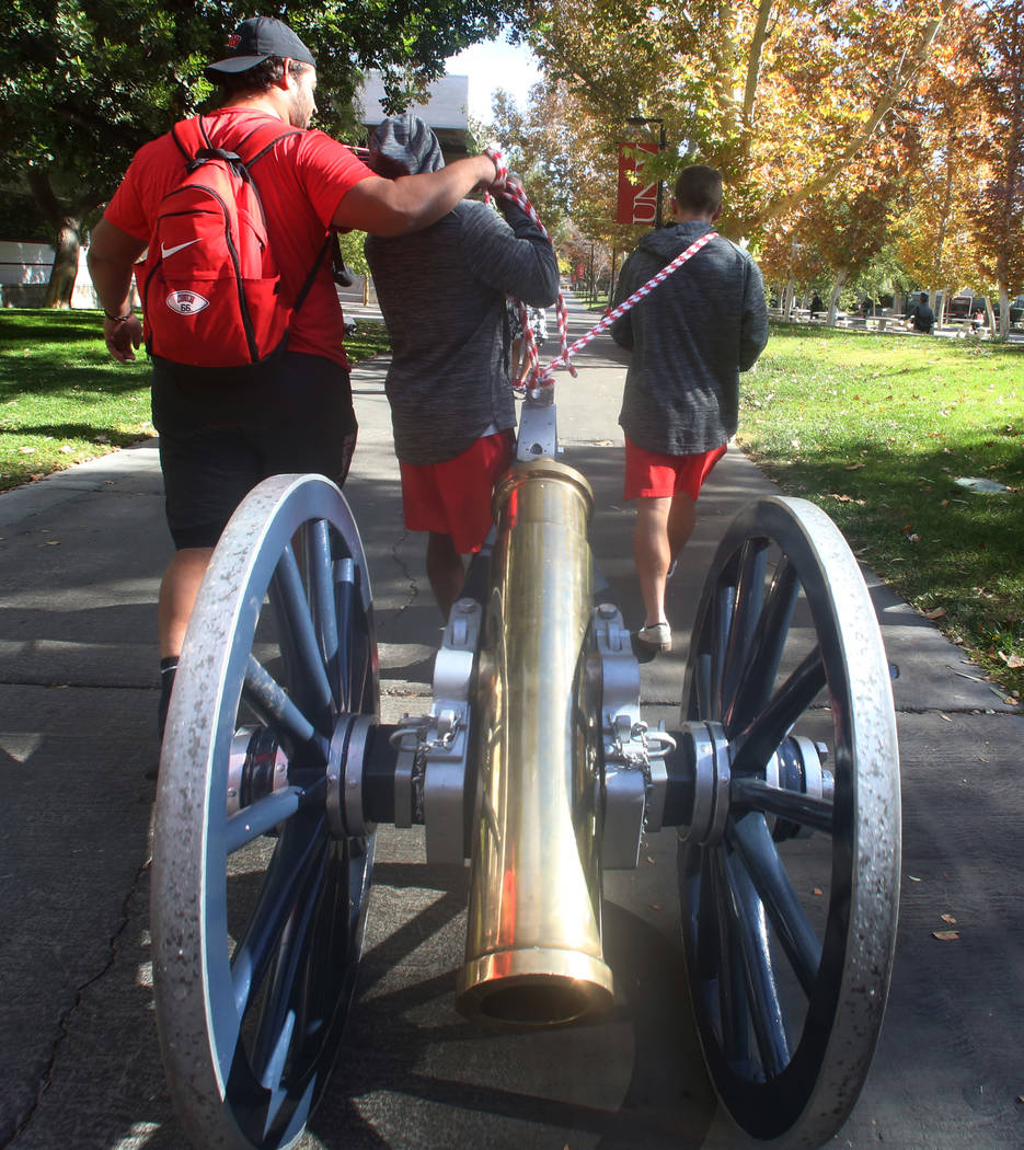 UNLV football players, including kicker Evan Pantels, right, pull the Fremont Cannon to be painted red outside of the Student Union at UNLV on Monday, Nov, 26, 2019, in celebration of their victo ...