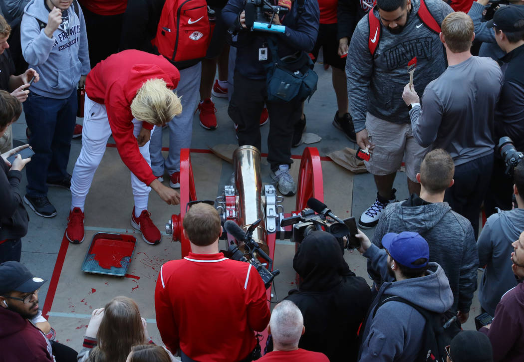 UNLV students and officials watch as Rebels players paint the Fremont Cannon red outside of the Student Union at UNLV on Monday, Nov, 26, 2019, in celebration of their victory against in-state riv ...