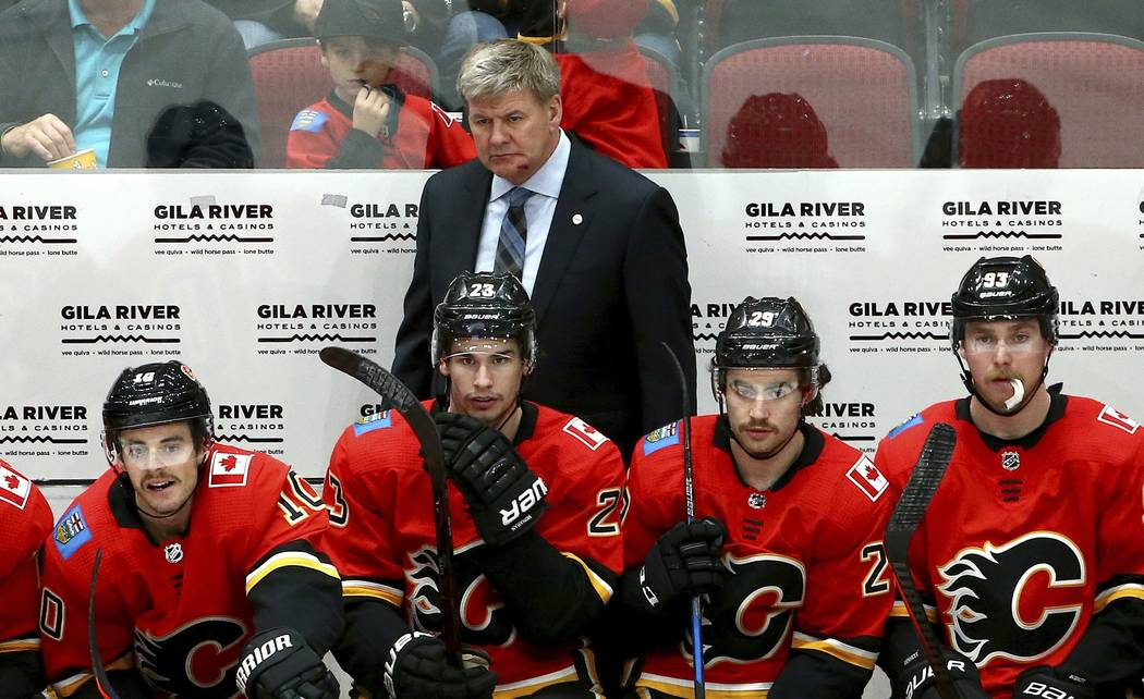 Calgary Flames head coach Bill Peters, top, returns to the bench with a gash on his chin after being hit with the puck earlier in the hockey game as he stands behind Flames center Derek Ryan (10), ...