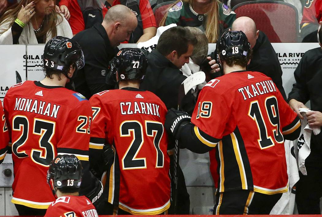 Calgary Flames center Sean Monahan (23), center Austin Czarnik (27) and left wing Matthew Tkachuk (19) look on as training staff treat head coach Bill Peters who was struck in the face with a puck ...