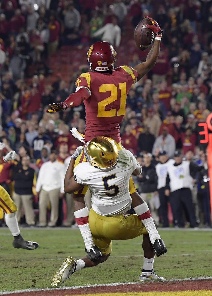 Southern California wide receiver Tyler Vaughns, top, makes a touchdown catch as Notre Dame cornerback Troy Pride Jr. tackles him during the second half of an NCAA college football game Saturday, ...