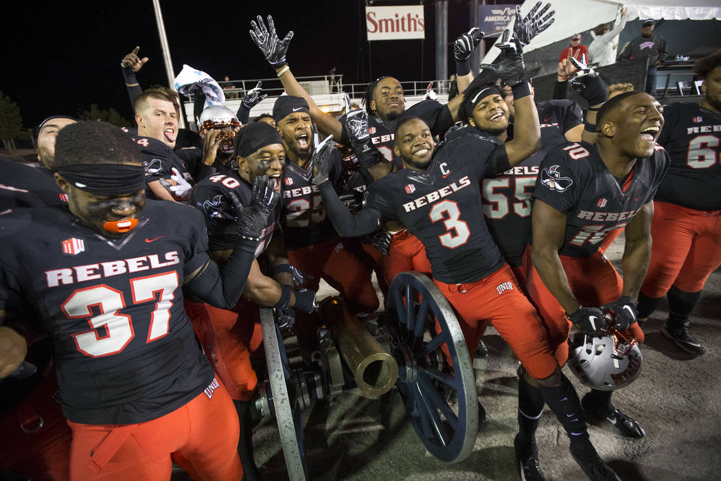 UNLV celebrates with the Fremont Cannon after defeating the Nevada Wolf Pack 34-29 following an NCAA football game at Sam Boyd Stadium in Las Vegas on Saturday, Nov. 24, 2018. Richard Brian Las Ve ...
