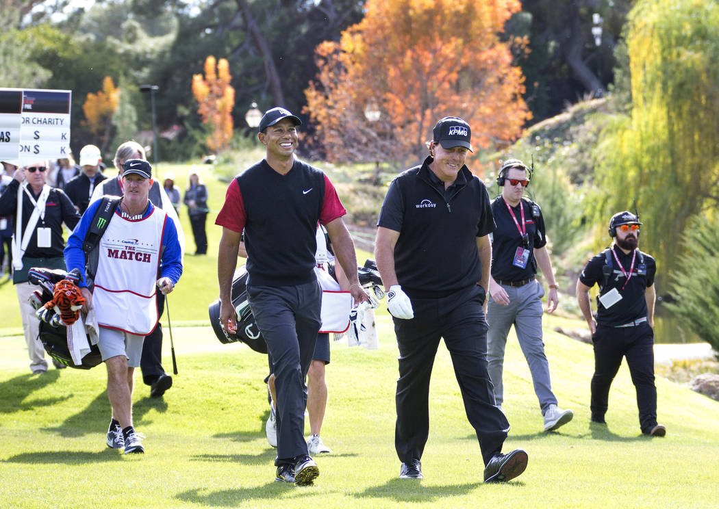 Tiger Woods, left, and Phil Mickelson walk to the fairway after teeing off from the first during The Match at Shadow Creek Golf Course in North Las Vegas on Friday, Nov. 23, 2018. Richard Brian La ...