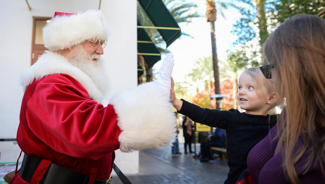 John Jones, dressed up as Santa Claus, high-fives Henderson resident Emilia Brodie, 2, along with mother Monica Brodie at the District at Green Valley Ranch in Henderson, Saturday, Nov. 24, 2018. ...