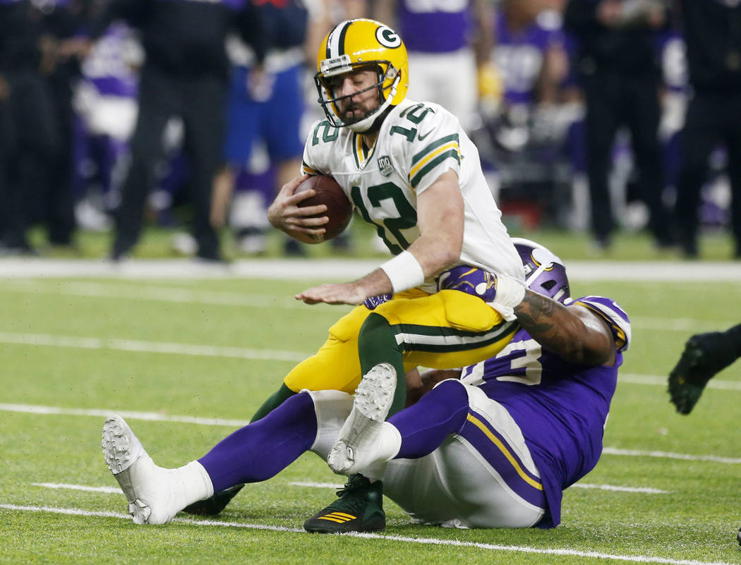 Green Bay Packers quarterback Aaron Rodgers is sacked by Minnesota Vikings defensive tackle Sheldon Richardson, right, during the second half of an NFL football game, Sunday, Nov. 25, 2018, in Min ...