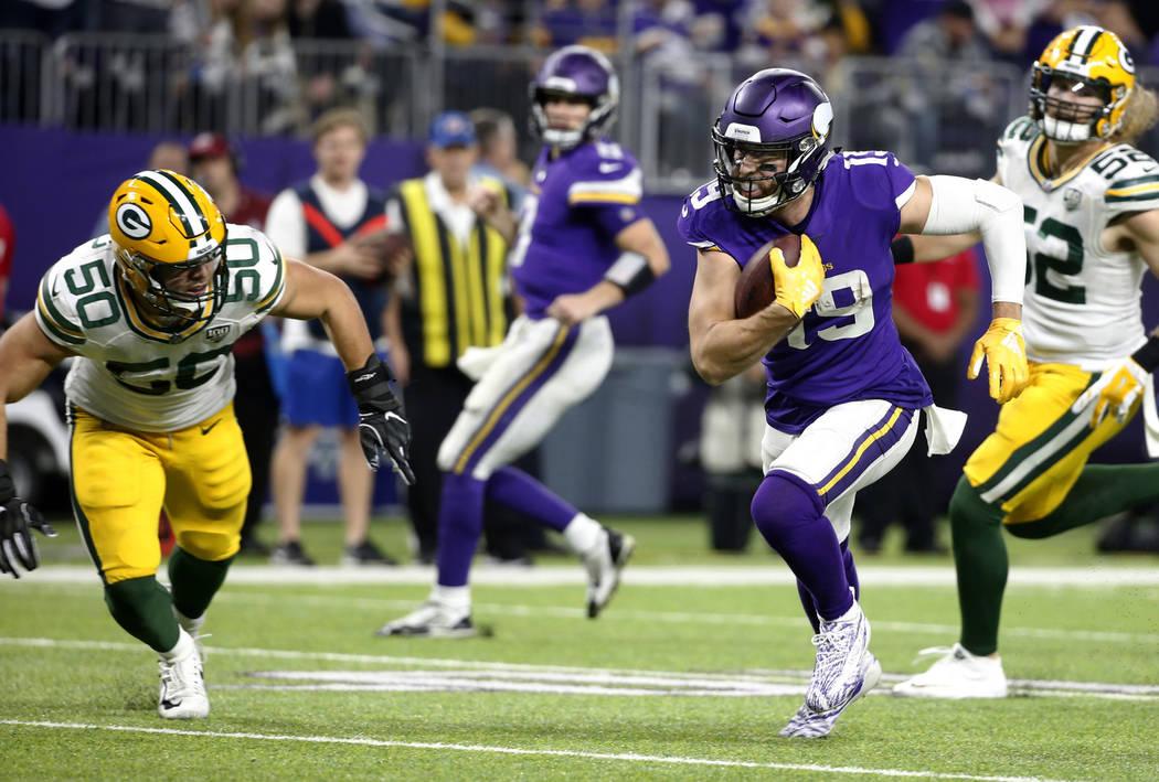 Minnesota Vikings wide receiver Adam Thielen (19) runs from Green Bay Packers inside linebacker Blake Martinez (50) with a 14-yard touchdown reception during the second half of an NFL football gam ...